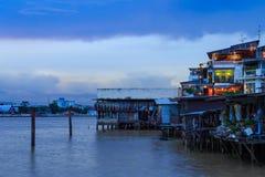 Comunità della riva del fiume a Chao Phraya River con le nuvole di pioggia Immagine Stock Libera da Diritti