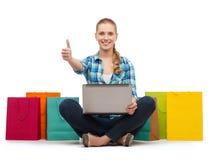 有膝上型计算机comuter和购物袋的微笑的女孩 免版税库存照片