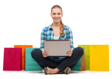 有膝上型计算机comuter和购物袋的微笑的女孩 库存照片