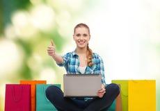 有膝上型计算机comuter和购物袋的微笑的女孩 免版税库存图片