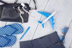 con el bolso azul, las gafas de sol, las chancletas, esmalte de uñas y poco aeroplano en el fondo de madera blanco Imágenes de archivo libres de regalías