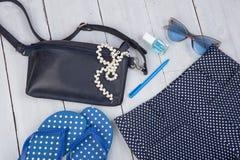 con el bolso azul, las gafas de sol, las chancletas, esmalte de uñas y poco aeroplano en el fondo de madera blanco Fotos de archivo libres de regalías