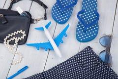 con el bolso azul, las gafas de sol, las chancletas, esmalte de uñas y poco aeroplano en el fondo de madera blanco Fotos de archivo