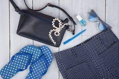 con el bolso azul, las gafas de sol, las chancletas, esmalte de uñas y poco aeroplano en el fondo de madera blanco Fotografía de archivo