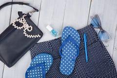 con el bolso azul, las gafas de sol, las chancletas, esmalte de uñas y poco aeroplano en el fondo de madera blanco Imagen de archivo libre de regalías