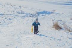 Con el canal para conducir en nieve la colina es un niño Foto de archivo