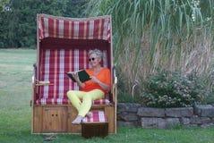 Con el libro en su mano, la mujer joven disfruta del día en la silla de playa de mimbre cubierta fotografía de archivo