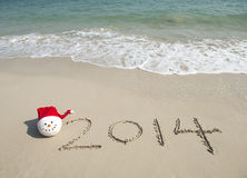 2014 con el muñeco de nieve de santa en la arena de la playa del mar Fotografía de archivo