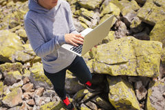 Con el ordenador portátil en piedras Fotografía de archivo libre de regalías