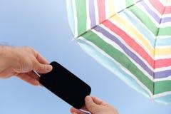 Con el teléfono debajo del parasol de playa Foto de archivo libre de regalías