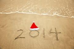 2014 con il cappello di Santa sulla sabbia della spiaggia del mare Fotografia Stock Libera da Diritti