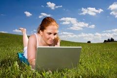 Con il computer portatile che si trova nell'erba Fotografia Stock Libera da Diritti