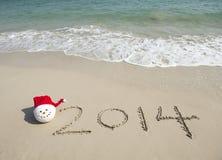 2014 con il pupazzo di neve di Santa sulla sabbia della spiaggia del mare Fotografia Stock