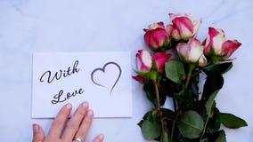 CON la tarjeta, el regalo y las flores de felicitación del AMOR en el tablero blanco, visión superior almacen de metraje de vídeo
