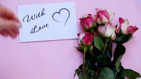 Con la tarjeta, el regalo y las flores de felicitación del amor en el tablero rosado, visión superior almacen de video