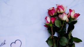 Con la tarjeta y las flores de felicitación del amor en el tablero blanco, visión superior almacen de video