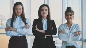 Con placer, tres mujeres de negocios cruzan sus brazos, mirando la cámara