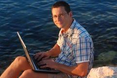 Con un computer portatile Fotografie Stock Libere da Diritti