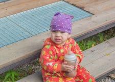 Con una botella de comida el bebé que mira la cámara Fotografía de archivo