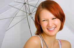 Con una sonrisa debajo de un paraguas foto de archivo libre de regalías