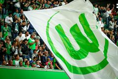 Con y bandera verde alrededor de las fans del VfL Wolfsburg durante un partido Fotografía de archivo
