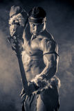 Conan barbarian. Portrait of a handsome muscular ancient warrior with a sword Stock Photography
