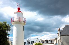 Landscapes and architectures of Brittany. Concarneau, France - August 10, 2017: View of the De La Croix lighthouse with black clouds in the background Royalty Free Stock Photo