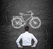 看有自行车的一个拉长的剪影的巨大的黑黑板一个商人的背面图在正式衣裳的 一conce 库存照片