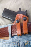 Concealed carry. Handgun in a leather waistband holster Stock Photos