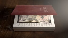 Concealed Notes In A Book. A red hardback book with a cutaway area in the pages concealing a stack of US dollar notes on an isolated background Royalty Free Stock Image