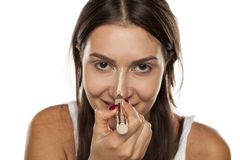 Concealer apply. Young woman applying concealer on her nose Stock Photo