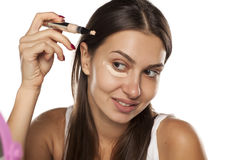 Concealer apply. Young woman applying concealer under her eyes with an applicator Royalty Free Stock Image