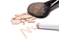 Concealer pencil and crushed compact cosmetic powder with makeup. Closeup of concealer pencil and crushed compact cosmetic powder with makeup brush on white royalty free stock image