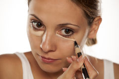 Concealer under her eyes. Young beautiful woman applying concealer under her eyes Stock Photo