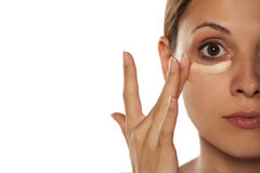 Concealer under her eyes. Young beautiful woman applying concealer under her eyes with her fingers Stock Photography