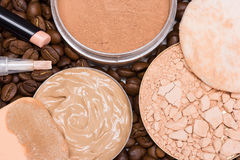 Concealers, foundation, powder on coffee beans Royalty Free Stock Photos