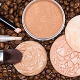 Concealers, foundation, powder on coffee beans Royalty Free Stock Image