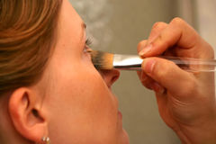 Concealing blemishes. Attractive young woman having make up applied by a beautician Stock Photo