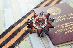 Conceda a guerra patriótica, a fita do ` s de StGeorge e o livro o da medalha Fotografia de Stock Royalty Free