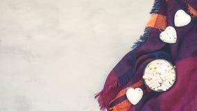 Conceito acolhedor do inverno, bandeira, modelo Café com os marshmallows no copo esmaltado e corações brancos decorativos em lãs  imagem de stock royalty free
