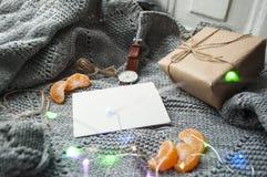 Conceito acolhedor do inverno Camiseta feita malha cinzenta, copo do chá, giftbox e relógios no fundo cinzento imagem de stock royalty free