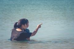 Conceito adorável e de família: Mulher e crianças que sentam-se no mar, eles que abraçam junto foto de stock