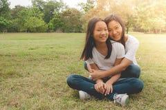 Conceito adorável: Felicidade de sorriso de aperto e de sentimento da mulher e da criança no parque imagens de stock