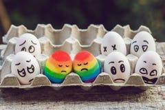 Conceito alegre da discriminação Dois ovos do arco-íris sob a forma de um par homossexual E povos de condenação ao redor imagem de stock
