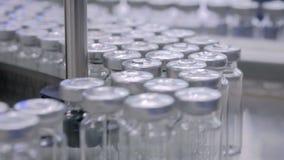 Conceito automatizado da tecnologia do pharma - correia transportadora com as garrafas de vidro vazias filme