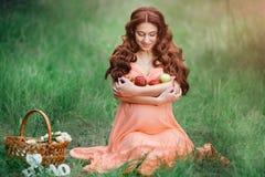 Conceito bonito da gravidez Mulher feliz moreno que senta-se na grama com cabelo encaracolado no fundo da natureza Imagens de Stock