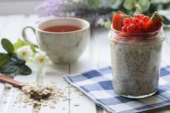 Conceito caseiro saudável do café da manhã: Farinha de aveia com sementes em um frasco de vidro Com bagas frescas imagem de stock