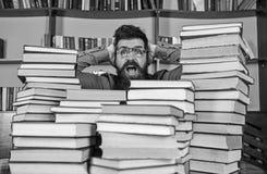 Conceito científico da descoberta Homem na cara chocada entre pilhas dos livros na biblioteca, estantes no fundo professor fotos de stock