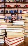Conceito científico da descoberta Homem na cara entusiasmado entre pilhas dos livros na biblioteca, estantes no fundo professor fotografia de stock royalty free