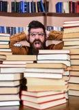 Conceito científico da descoberta O professor ou o estudante com barba vestem monóculos, sentam-se na tabela com os livros, defoc fotos de stock